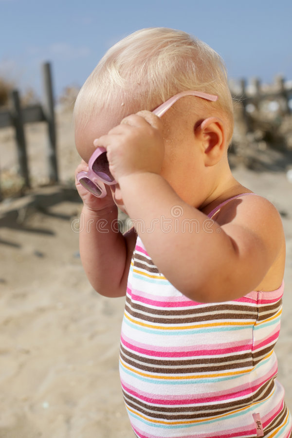 Beautiful Baby Girl. Wearing a swimsuit, taking her sunglasses off stock photos