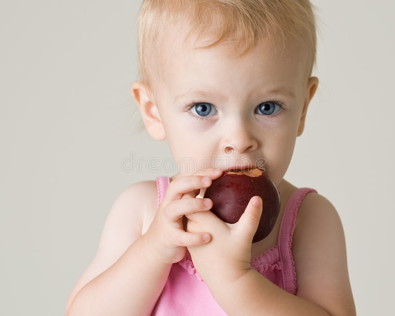 Beautiful baby girl eating a plum stock photo