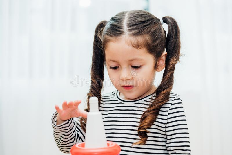Beautiful baby girl kindergarten playing loop toy education. At interior home before preschool royalty free stock photography