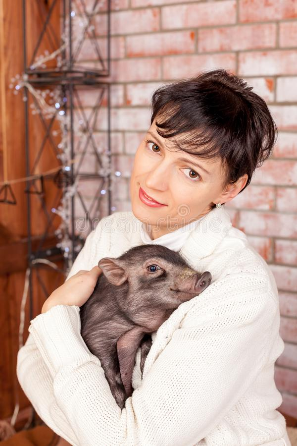 Beautiful smiling woman near a Christmas tree holding in hands black vietnamese piglet. Concept of the Chinese New Year royalty free stock photos