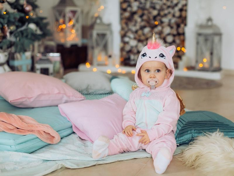 Beautiful baby girl near a Christmas tree with gifts stock image