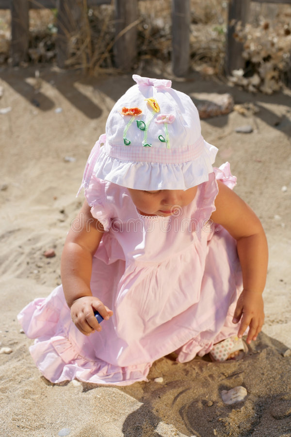 Beautiful Baby Girl Playing on the Beach. Beautiful Baby Girl wearing a hat playing on the Beach royalty free stock photography