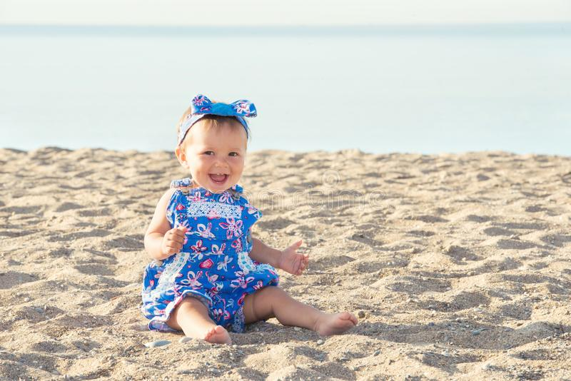Beautiful baby girl playing on the sand by the sea royalty free stock photos