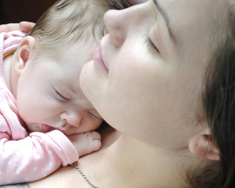 Beautiful baby girl sleeping. With mother stock images