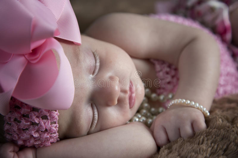Beautiful baby girl sleeping. Beautiful little baby girl with bow and pearls sleeping peacefully on fur blanket stock photos