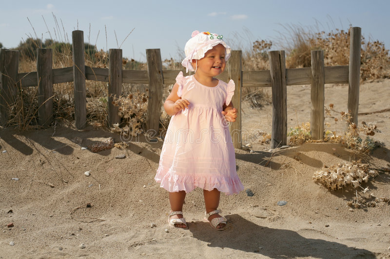 Beautiful Baby Girl Smiling. Standing at the Fence stock photography
