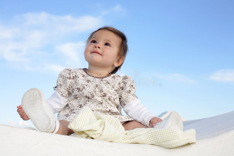 Beautiful baby girl smiling. Beautiful baby girl sitting on a wall smiling and having fun stock photos