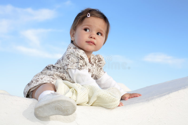 Beautiful baby girl smiling. Beautiful baby girl sitting on a wall smiling and having fun stock images