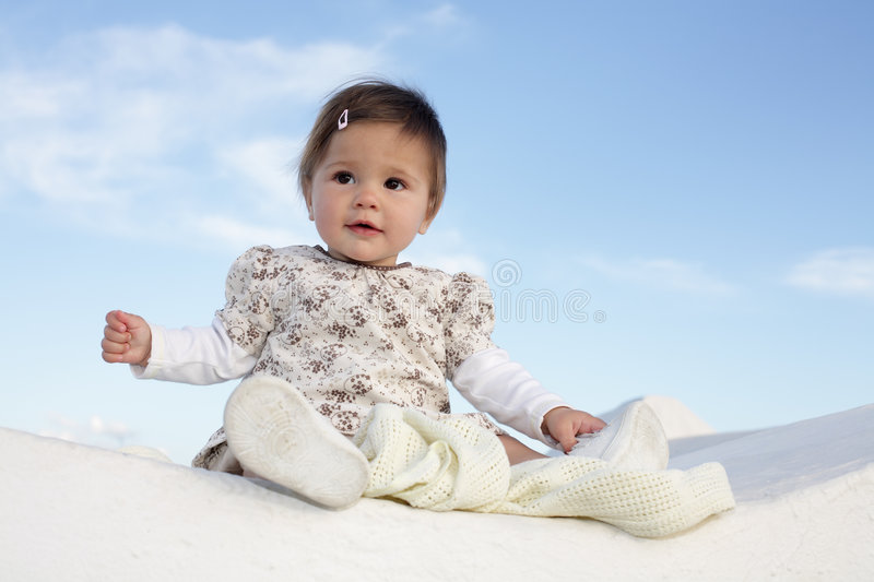 Beautiful baby girl smiling. Beautiful baby girl sitting on a wall smiling and having fun royalty free stock images