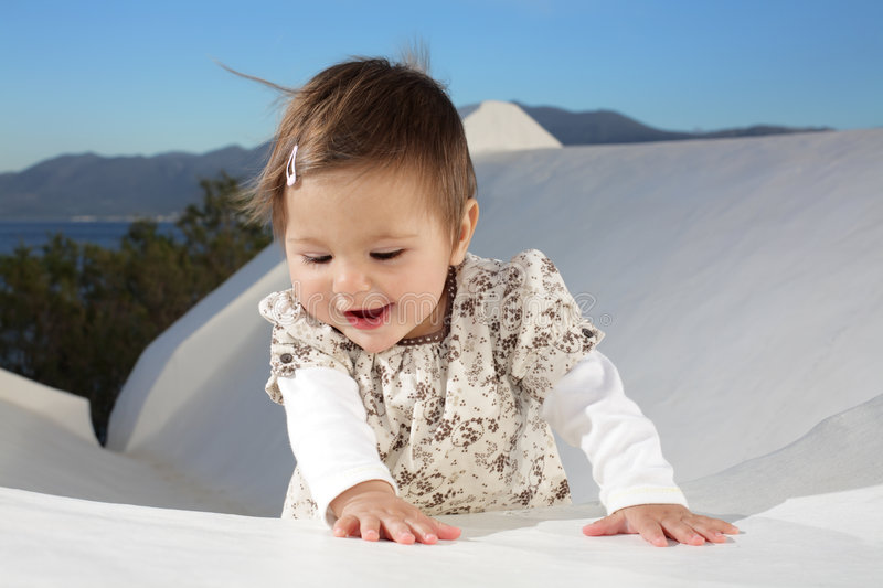 Beautiful baby girl smiling. Beautiful baby girl sitting on a wall smiling and having fun stock photo