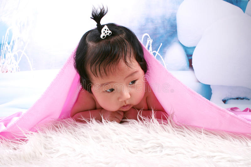 Beautiful baby girl under blanket royalty free stock photography