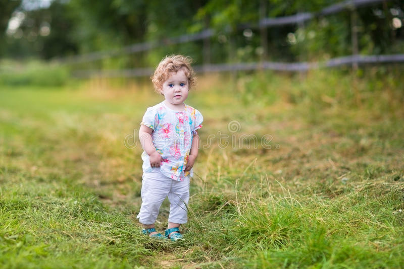 Beautiful Baby Girl Walking On Country Road At Sunset Stock Photo
