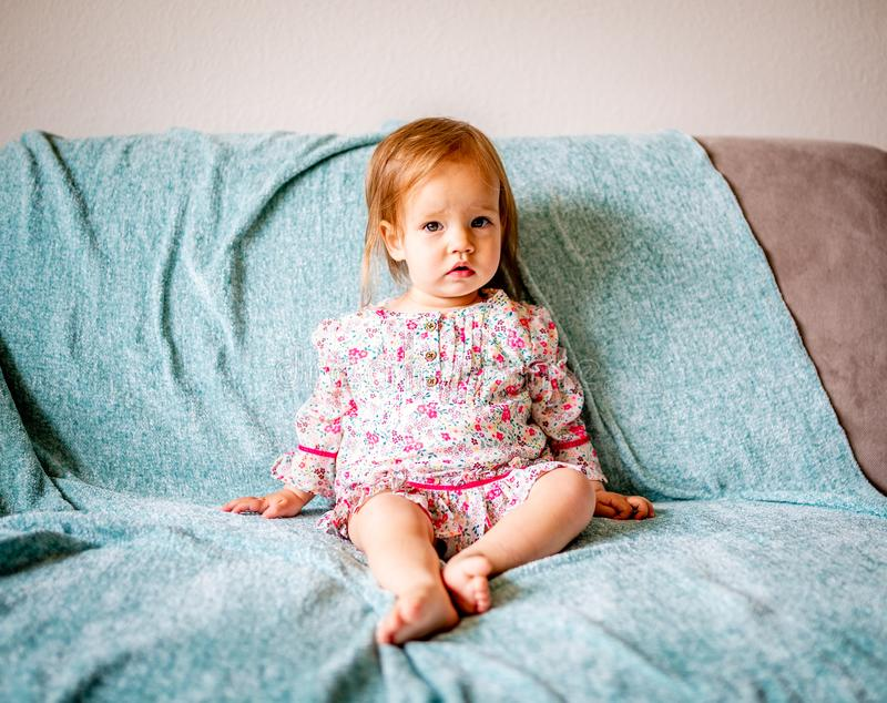 Adorable Baby Girl Sits on Couch royalty free stock images