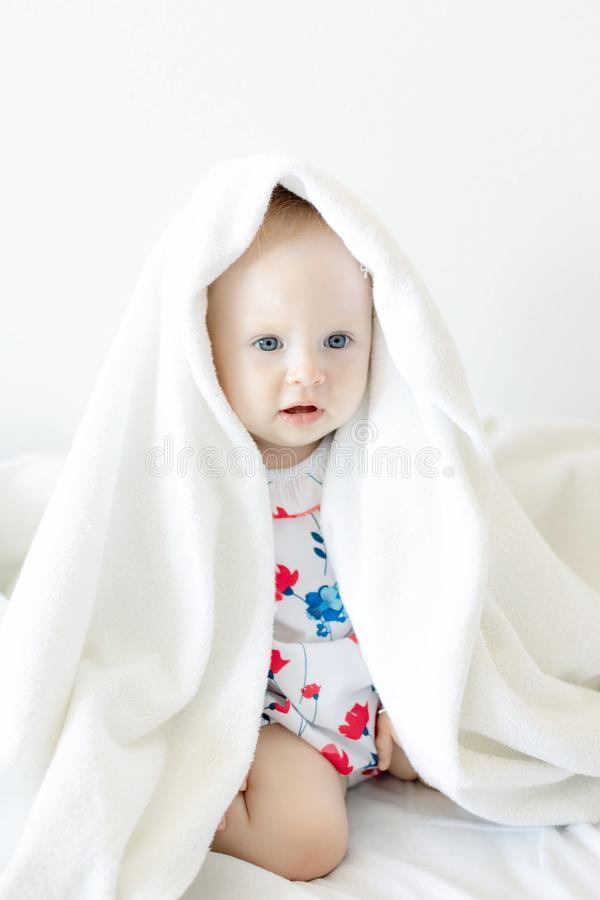 Beautiful baby kid Peeps out from under the sheets and fervently plays posing for the camera stock photos