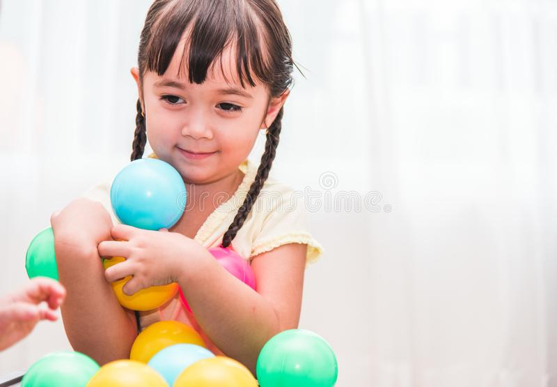 Beautiful baby kids girl kindergarten playing colorful ball royalty free stock photography