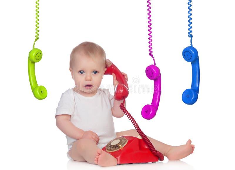 Beautiful baby with many telephones royalty free stock photo