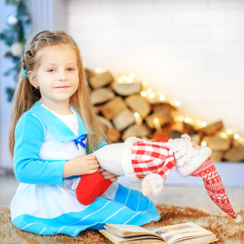 A beautiful baby is playing a toy on the floor. Concept New Year. Merry Christmas, holiday, vacation, winter, childhood royalty free stock photos