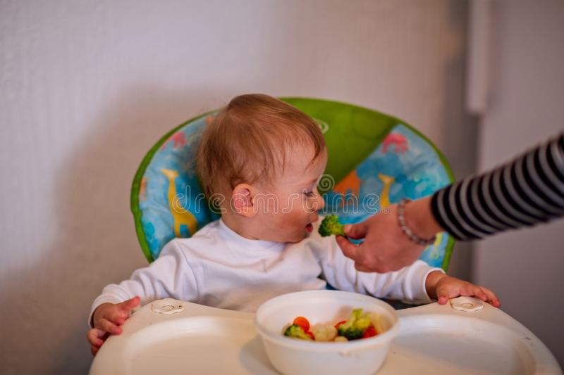 Beautiful baby refuses to eat vegetable. Beautiful baby boy refuses to eat vegetable royalty free stock image