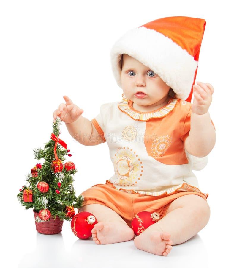 Beautiful baby in santa hat near christmas tree stock images