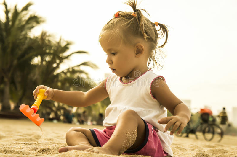 Beautiful baby sits facing the camera and playing with toy rake in the sand on the beach. royalty free stock image