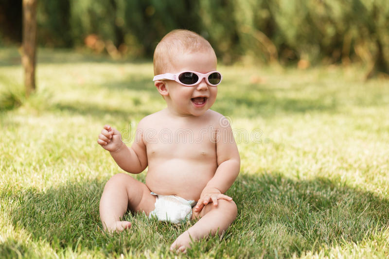 Beautiful baby sitting on green grass outdoors stock photography