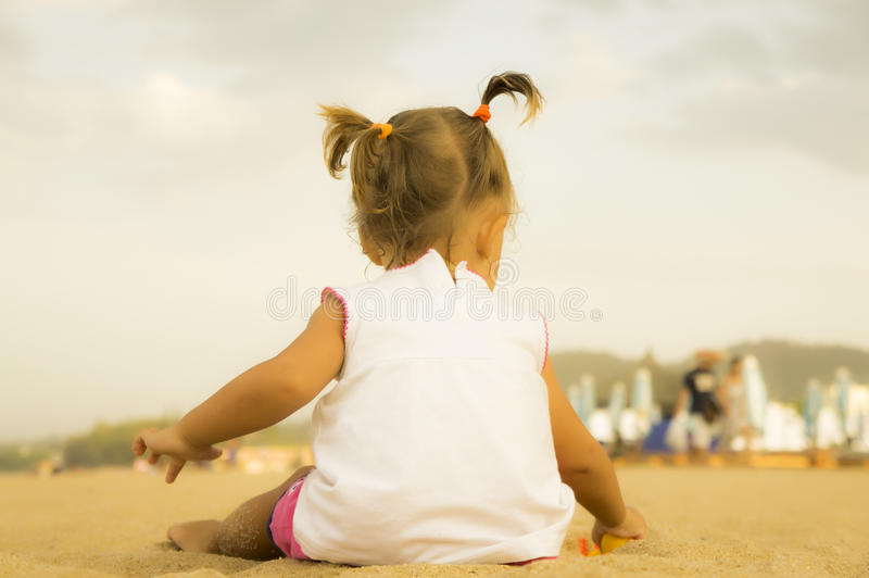 Beautiful baby sitting with his back to the camera and playing with a toy rake in the sand on the beach. stock images