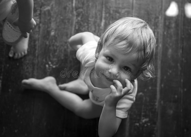 Beautiful baby sitting in summer on hut on wooden floor. With barefooted stock photography
