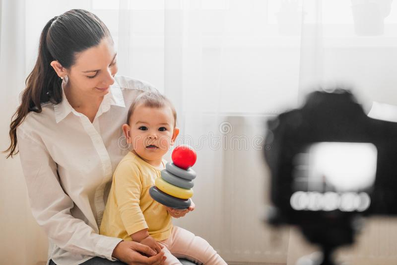 Beautiful baby toddler with young mother in front of the camera vlogging or blogging indoors stock photography