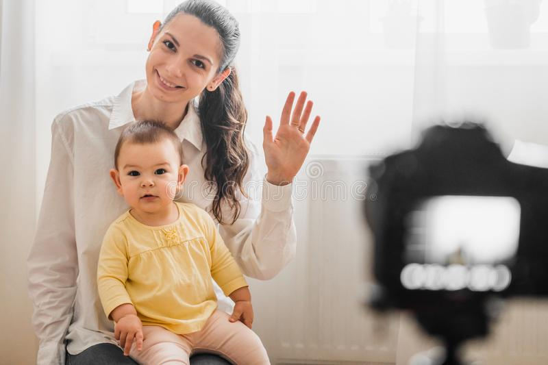 Beautiful baby toddler with young mother in front of the camera vlogging or blogging indoors royalty free stock photo