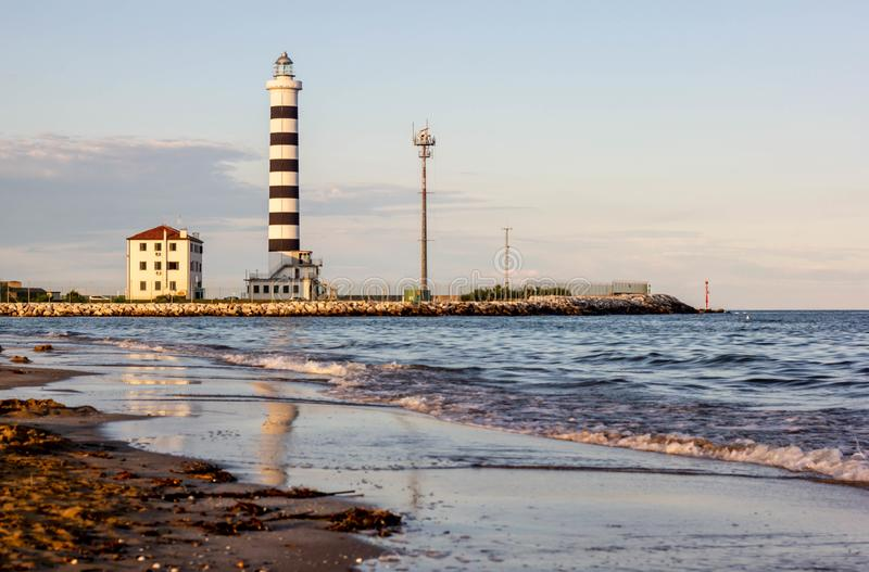 Beautiful background with images of a wonderful beach and a beautiful sea   . lighthouse on the shores of Jesolo beach at sunset. Beautiful background with stock photos
