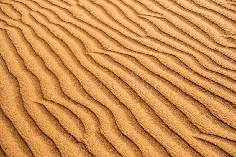 Desert sand textured patterns naturally done by wind. Beautiful background textured patterns in the desert sand dunes. Patterns caused by wind stock photo
