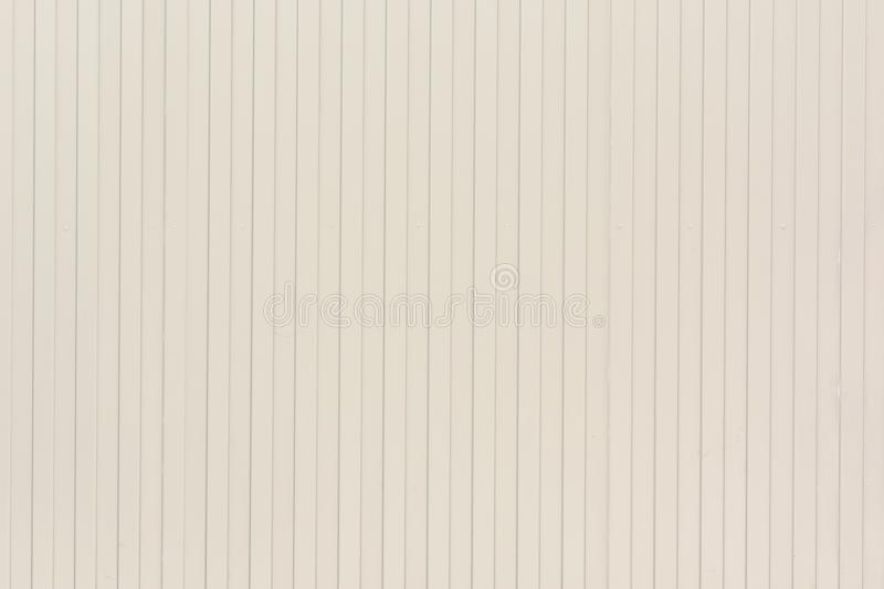 Background of vertical lines of lines. Pale beige wall of unusual stripes, laths. stock photos