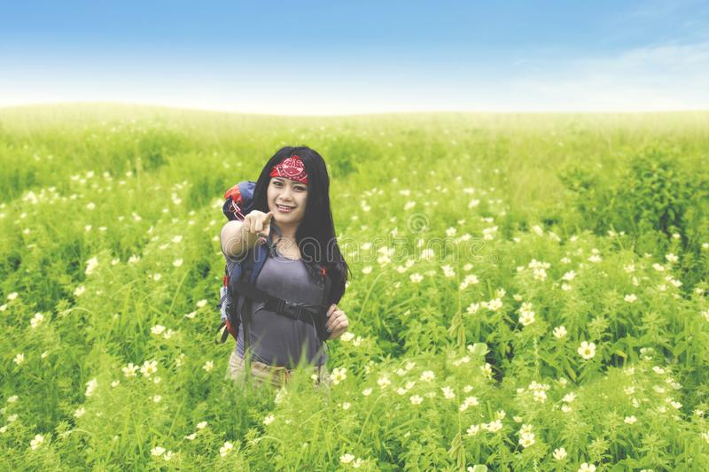 Beautiful backpacker pointing at you in flower field stock photos
