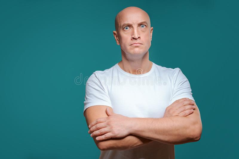 Beautiful bald serious man in white t-shirt on blue background royalty free stock photo