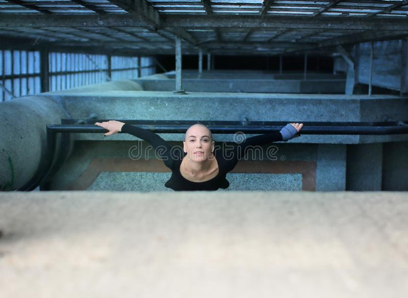 Beautiful bald woman looking up from the floor below and leaning on a railing royalty free stock photography