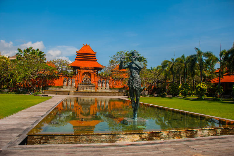 Beautiful Balinese building with a fountain and sculpture-man playing the flute. Tanjung Benoa. Nusa Dua, Bali. Beautiful Balinese building with a fountain and royalty free stock photography