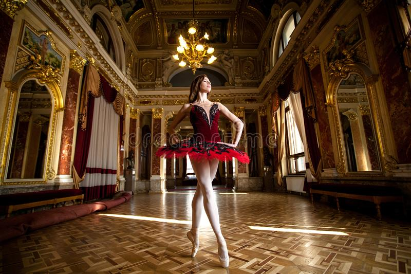 Beautiful ballerina dancing in a luxurious hall in a red dress stock photo