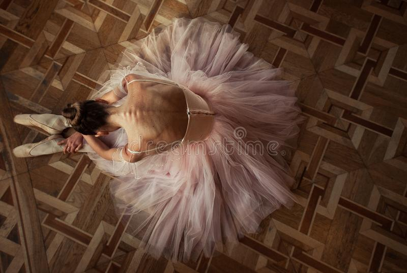 Beautiful ballerina sitting on the floor in a pink dress. Top view stock photos