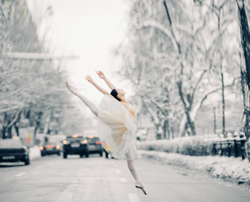 Beautiful ballerina is dancing and jumping on snowy street among cars royalty free stock photography