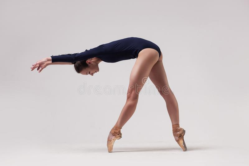 Beautiful ballet dancer. Beautiful woman ballet dancer in black swimsuit posing on light grey studio background stock photography