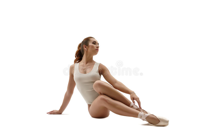 Beautiful ballet dancer sitting. Isolated on white. Background royalty free stock photos