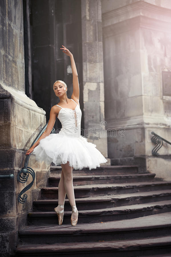 Beautiful ballet woman on stairs. Catching last sun beams. Portrait of a ballerina performing outdoors near an old building stock photography
