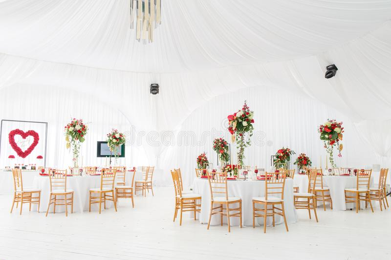 Beautiful banquet hall under a tent for a wedding reception. Interior of a wedding tent decoration ready for guests stock photos