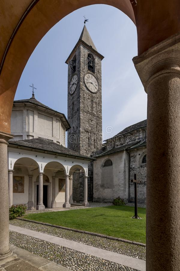 The beautiful baptistery and the bell tower of Baveno, Italy, framed by the columns of the portico of the via crucis. The beautiful baptistery and the bell tower stock images