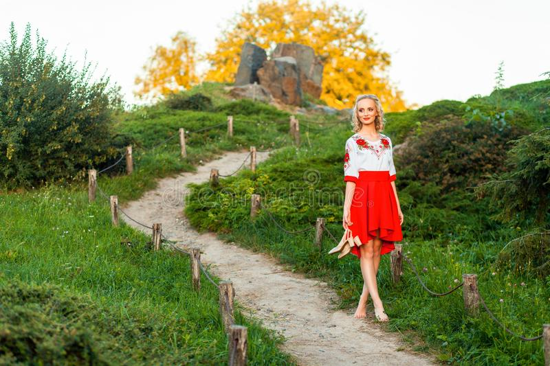 Beautiful barefoot woman in stylish red white dress holding shoes in hand and walking on path at hill. standing on road village royalty free stock photos