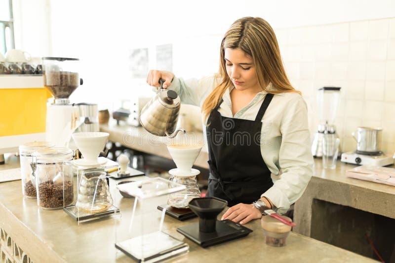 Beautiful barista brewing some coffee royalty free stock photo