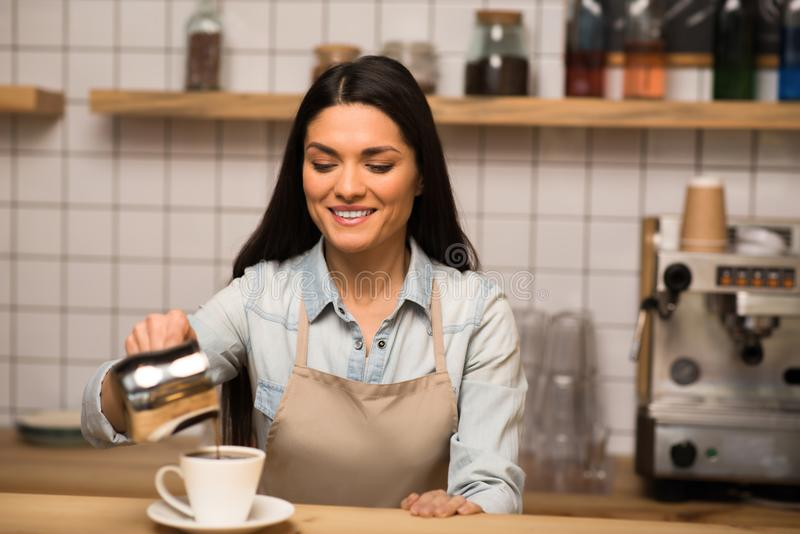 Barista pouring coffee. Beautiful barista pouring coffee into the cup royalty free stock image