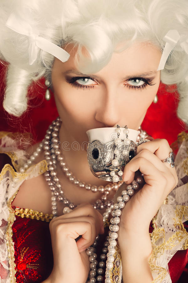 Beautiful Baroque Woman Portrait Drinking from a Cup stock photo