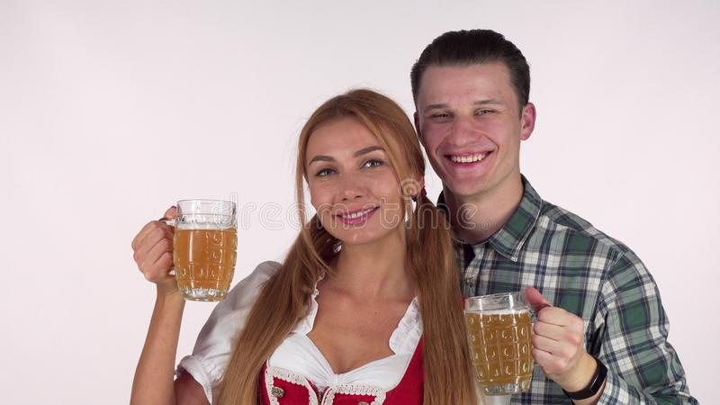 Beautiful Bavarian couple celebrating Oktoberfest, drinking beer together royalty free stock photography