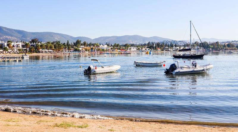 Beautiful bay with calm water, sandy beach, boats and yachts. Small town and green mountains on the coast of the Aegean sea stock photography